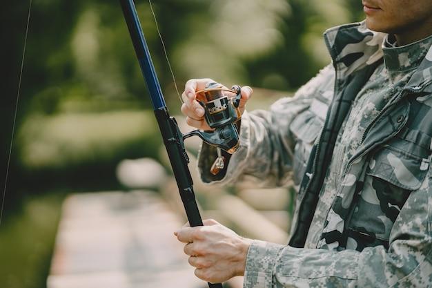 Mann fischt und hält die angelrute Kostenlose Fotos