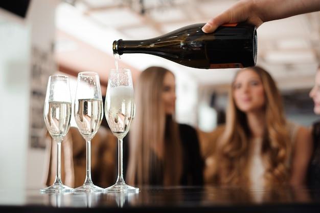 Mann füllt gläser champagner für drei schöne junge frauen Premium Fotos