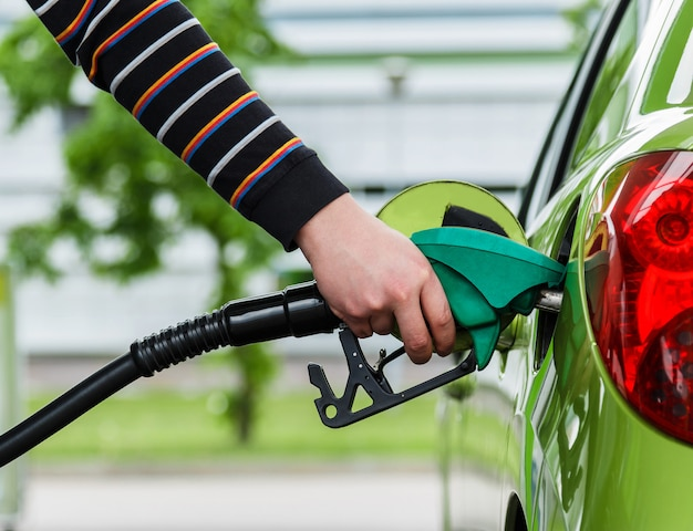 Mann füllt sein auto mit benzin auf Premium Fotos