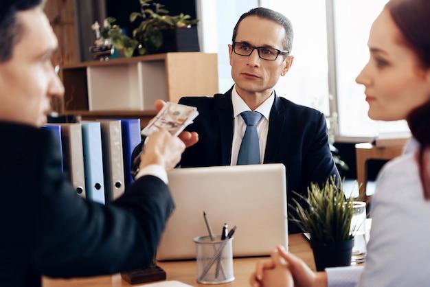 Mann gibt dem rechtsanwalt geld für die scheidung und sitzt im büro. Premium Fotos