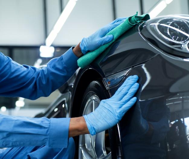 Mann hält die mikrofaser in der hand und poliert das auto Premium Fotos
