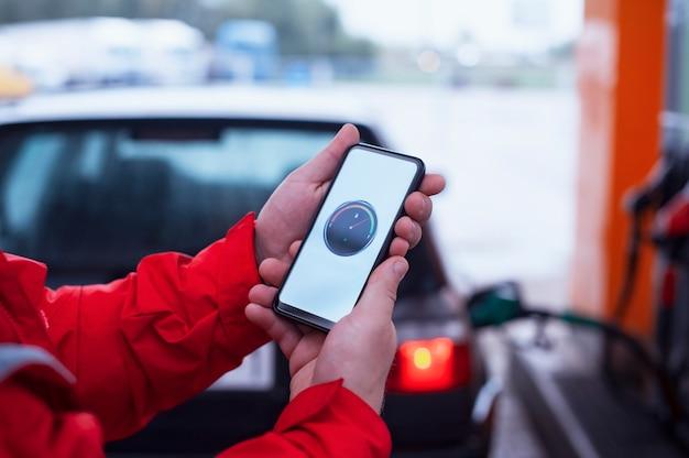 Mann hält ein smartphone mit einem digitalen kraftstoffzähler auf dem bildschirm im hintergrund Premium Fotos