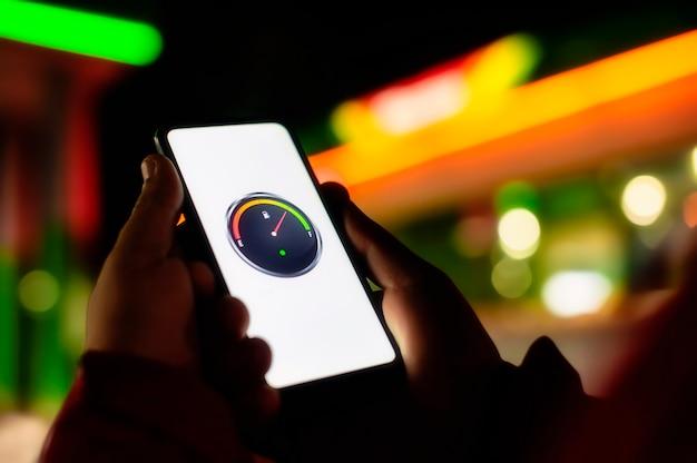 Mann hält ein smartphone mit einem digitalen kraftstoffzähler auf dem bildschirm vor dem hintergrund einer nachttankstelle für ein auto. Premium Fotos