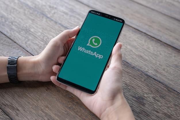 Mann hält ein smartphone mit offener whatsapp auf dem bildschirm. Premium Fotos