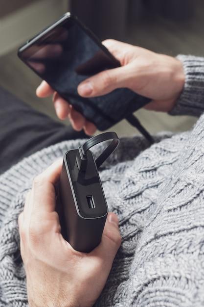 Mann hält ein telefon und eine powerbank Premium Fotos