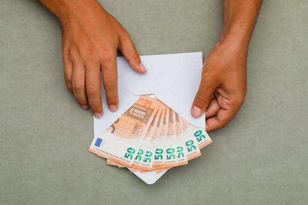 Mann hält umschlag voller banknoten. Kostenlose Fotos