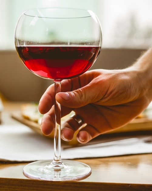 Mann halten das glas mit rotweinseitenansicht Kostenlose Fotos