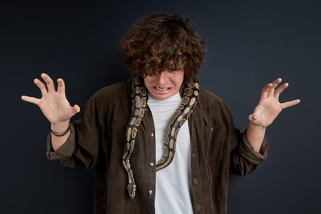 Mann hat eine panikattacke mit schlange auf den schultern, verwirrter kerl kann sich nicht bewegen, macht lustvolles gesicht aus angst Premium Fotos