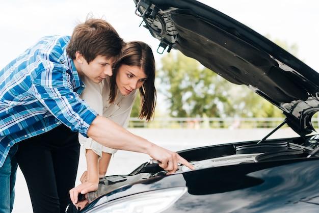 Mann helfende frau reparieren auto Kostenlose Fotos