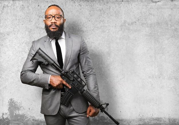 Mann im anzug mit einem maschinengewehr Kostenlose Fotos
