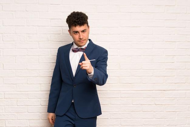 Mann im anzug und in der fliege frustriert und auf die front zeigend Premium Fotos