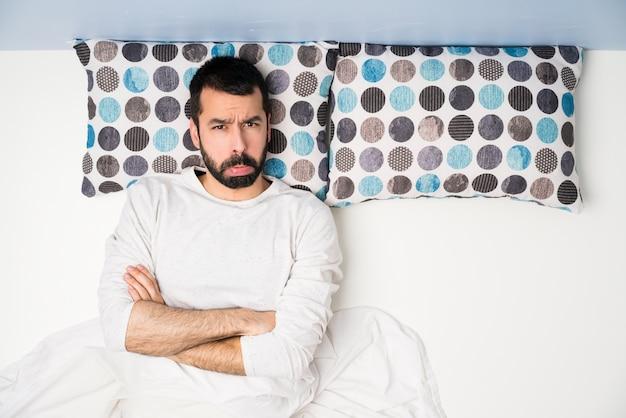 Mann im bett in der draufsicht mit traurigem und deprimiertem ausdruck Premium Fotos