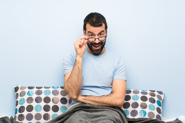 Mann im bett mit brille und überrascht Premium Fotos