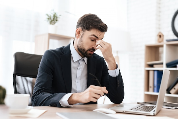 Mann im büro sitzt und hält seinen kopf in den schmerz. Premium Fotos