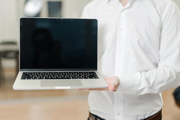 Mann im büro zeigt laptop mit leerem bildschirm Premium Fotos