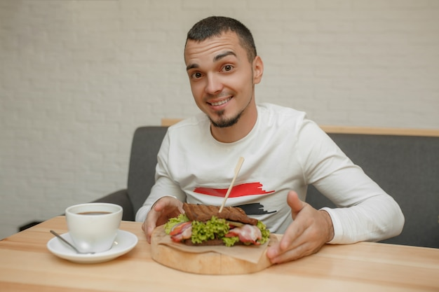 Mann im café isst sandwich Premium Fotos