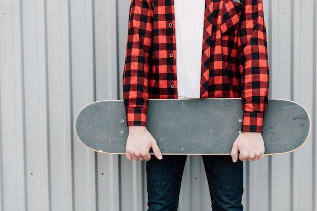 Mann im flanellhemd, das skateboard hält Kostenlose Fotos