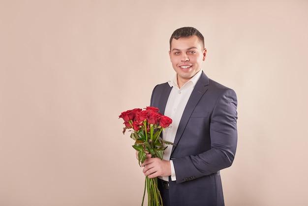 Mann im grauen anzug mit roten rosen Premium Fotos