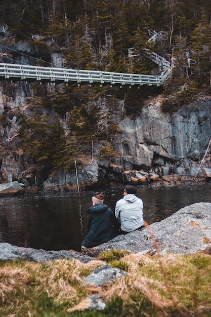 Mann im grauen kapuzenpulli, der auf felsen nahe dem gewässer während des tages sitzt Kostenlose Fotos