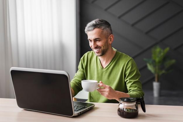 Mann im grünen hemd lächelt und benutzt seinen laptop Kostenlose Fotos