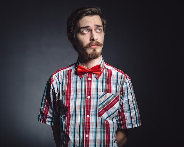 Mann im karierten hemd und in der fliege im studio Kostenlose Fotos