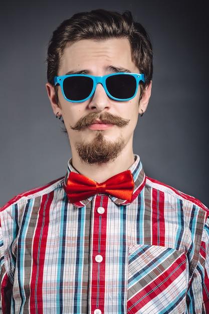 Mann im karierten hemd und in der fliege mit gläsern im studio Kostenlose Fotos