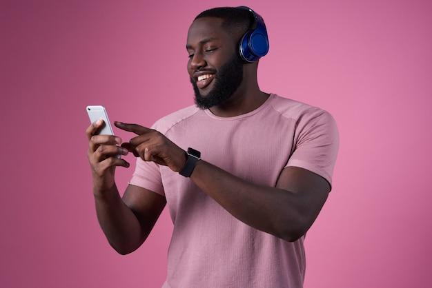Mann im kopfhörer und mit telefon in seinen händen schaltet musik Premium Fotos