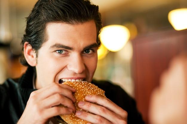 Mann im restaurant hamburger essend Premium Fotos