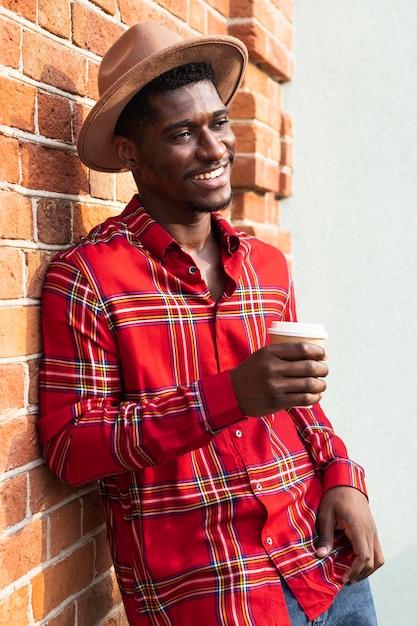 Mann im roten hemd, das an eine wand lehnt und einen kaffee hält Kostenlose Fotos