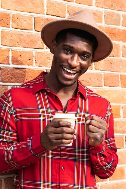 Mann im roten hemd lächelt und hält kaffee Kostenlose Fotos