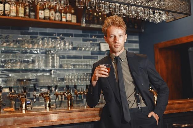 Mann im schwarzen anzug trinkt alkohol. attraktiver typ trinkt whisky aus einem glas .. Kostenlose Fotos