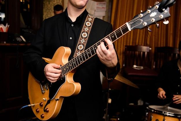 Mann im schwarzen hemd spielt auf gitarre Kostenlose Fotos