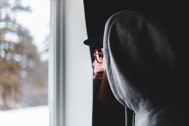 Mann im schwarzen hut und im grauen kapuzenpulli Kostenlose Fotos