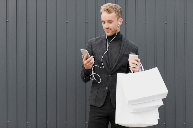 Mann im schwarzen mit dem kaffee, der smartphone betrachtet Kostenlose Fotos