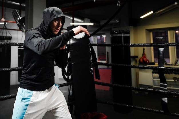 Mann im sportkleidungstraining im boxring mit kopienraum Kostenlose Fotos