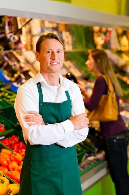 Mann im supermarkt als verkäufer Premium Fotos