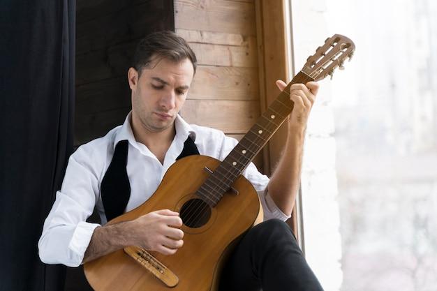 Mann im weißen hemd, das die gitarre spielt Kostenlose Fotos
