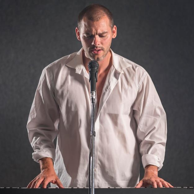 Mann im weißen hemd, das tastaturen spielt und singt Kostenlose Fotos