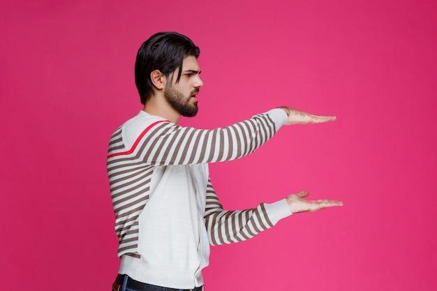 Mann im weißen hemd, der die maße eines pakets demonstriert. Kostenlose Fotos