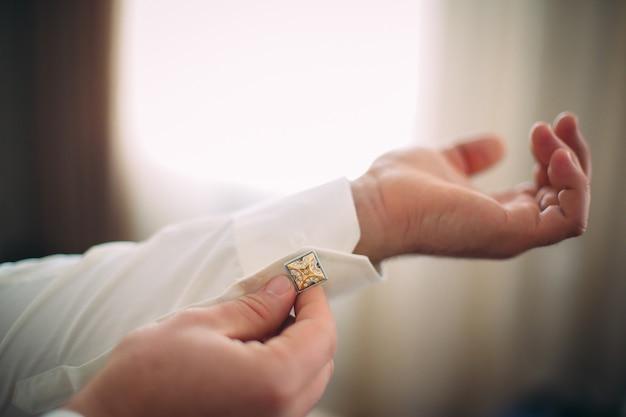 Mann im weißen hemd, der einen bolzen befestigt. konzept eines morgens des jungen mannes. Premium Fotos