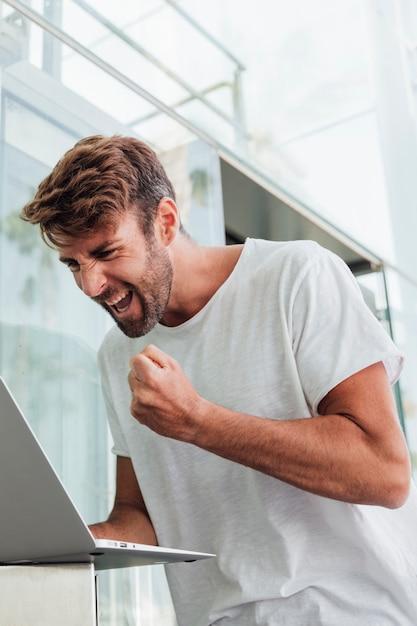 Mann im weißen t-shirt mit laptop feiernd Kostenlose Fotos