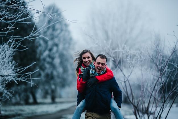Mann im winterkleid mit seiner freundin in den rücken Kostenlose Fotos