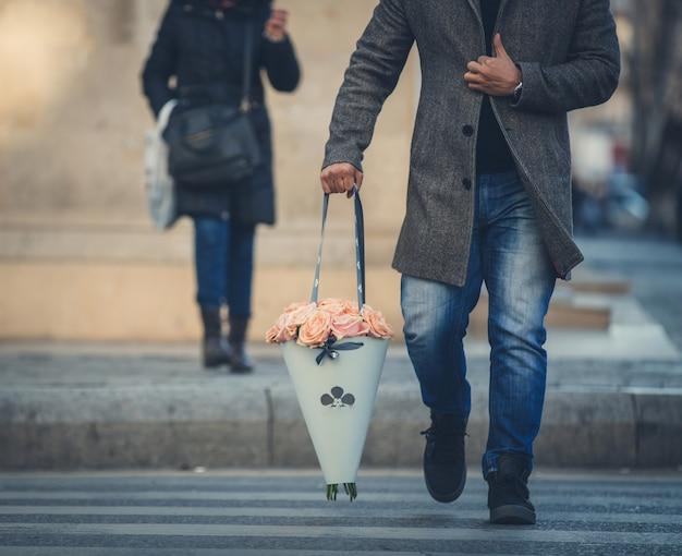 Mann im wtreet gehend mit einem tragbaren blumenblumenstrauß. Kostenlose Fotos
