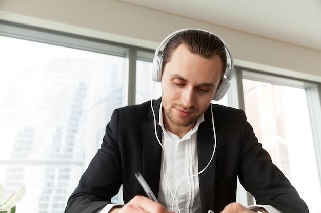 Mann in den kopfhörern schreibend mit stift am arbeitsschreibtisch Kostenlose Fotos