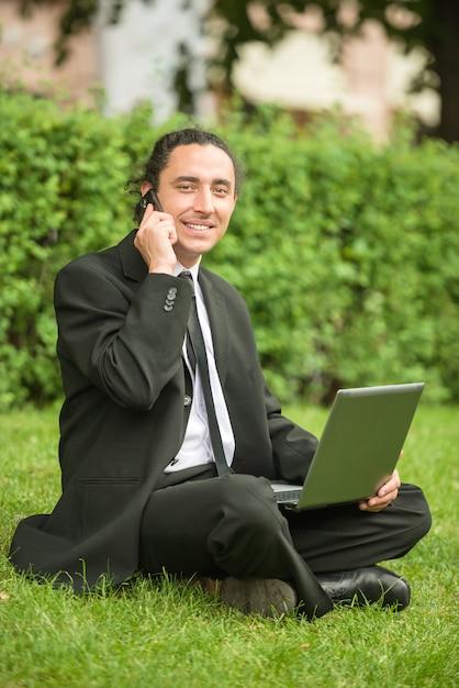 Mann in der klage, die am rasen mit laptop sitzt. Premium Fotos