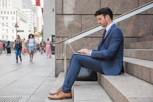 Mann in der klage, die laptop auf straße verwendet Kostenlose Fotos