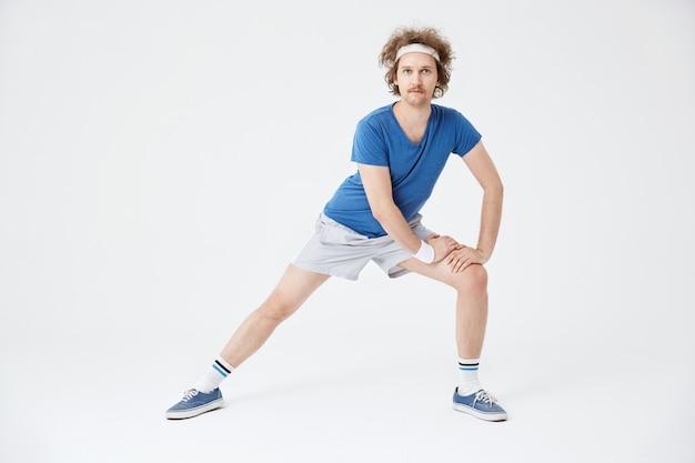 Mann in der retro-sportbekleidung, die muskeln vor dem training aufwärmt Kostenlose Fotos