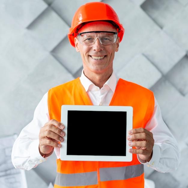 Mann in der sicherheitsausrüstung, die ein tablettenmodell zeigt Kostenlose Fotos
