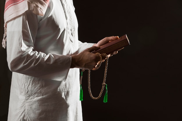 Mann in der traditionellen arabischen kleidung, die quran hält Kostenlose Fotos