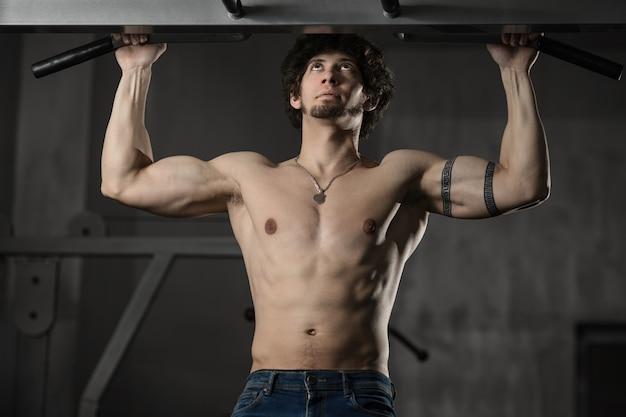 Mann in der turnhalle, die pull-upbodybuildertraining in der turnhalle macht Premium Fotos